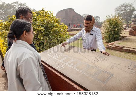 Archaeological heritage of India ruins of university of Nalanda on February 2 2014. At a stone with the scheme of excavation the Indian guide shows to tourists an sites of objects.