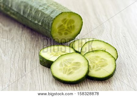 sliced cucumber on a wooden textured background in morning window light