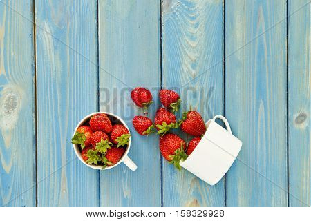 two cups of tasty sweet fresh strawberries on a light blue wooden textured background