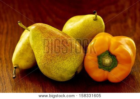 Fresh pears and a sweet yellow pepper on a textured wooden background