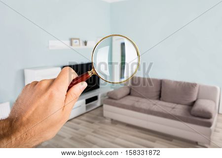 Close-up Of Person Hand Checking Living Room Using Magnifying Glass In House