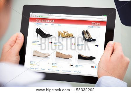 Close-up Of Person Purchasing Footwear While Doing Online Shopping On Digital Tablet