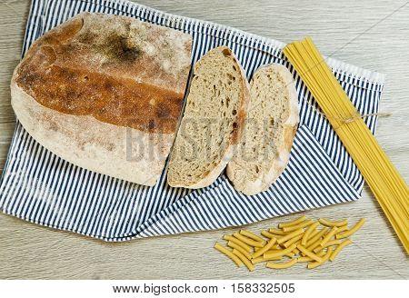 Fresh ciabatta bread and spaghetti pasta on a wooden textured background