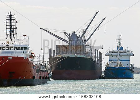 Large cargo ships off loading in a harbor or port