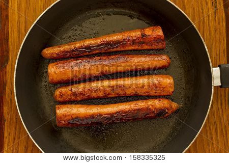 Roasted fresh carrots in butter in a pan on a wooden cutting board
