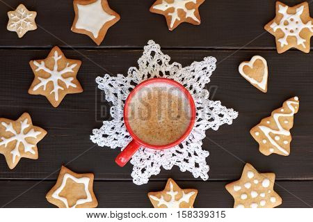 flat layout with red mug full of frothy coffee surrounded by a shaped cookies top view / festive coffee break