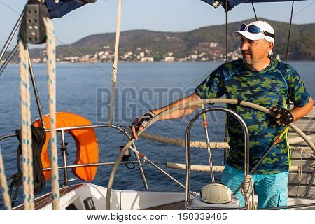A man stands at the helm and operates the sailing vessel.