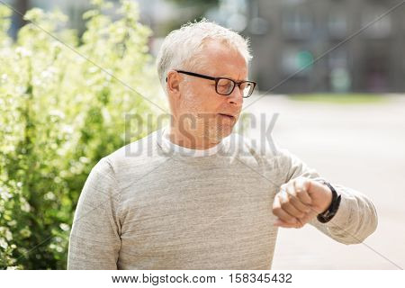 punctuality and people concept - senior man checking time on his wristwatch or smartwatch in city