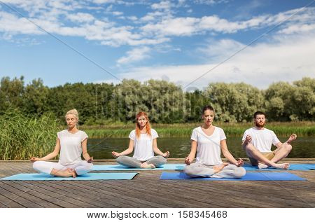 fitness, sport, yoga and healthy lifestyle concept - group of people meditating in lotus pose on river or lake berth