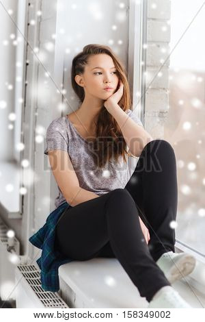 people, winter, christmas and teens concept - sad unhappy pretty teenage girl sitting on windowsill and looking through window over snow
