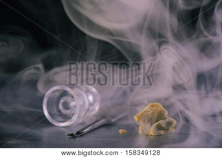 Marijuana extraction concentrate aka wax crumble on dark background with tool and glass rig