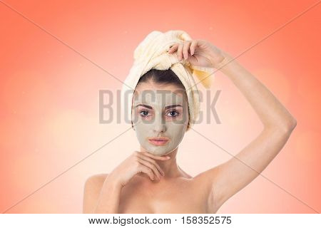 beauty girl takes care her skin with cleansing mask on face and towel on head isolated on white background. Health care concept. Body care concept. Young woman with healthy skin.