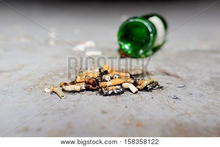 remnants of cigarettes and a bottle of wine