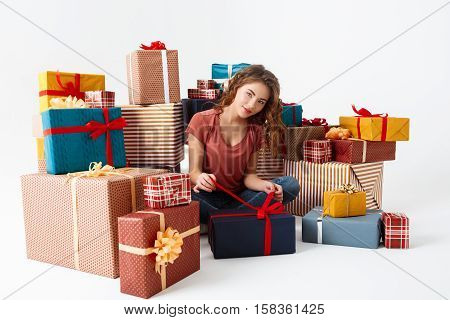 Young beautiful curly girl sitting on floor among gift boxes opening one of them Isolated Copy space