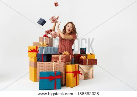 Young surprised beautiful curly girl among lying and falling gift boxes Isolated Copy space
