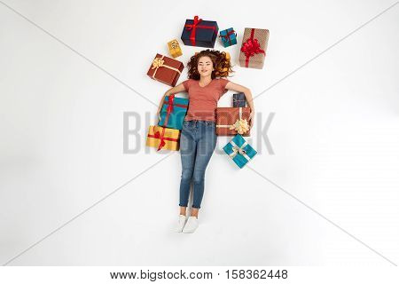 Young beautiful curly girl lying on floor among gift boxes Shot from above Isolated Copy space