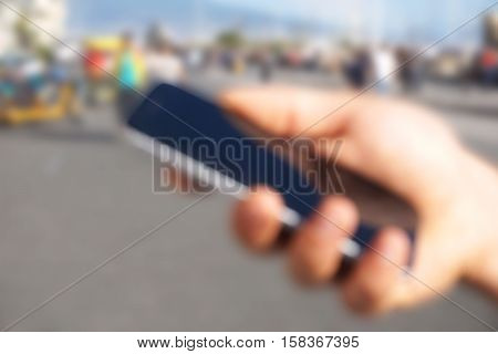 Male hand holding modern smartphone with black screen in the city center  - De focused image - Urban and people in the background - Concept about people and technology