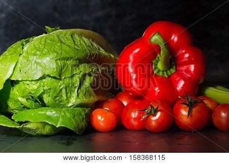 raw lettuce, red peppers and tomatoes on black background