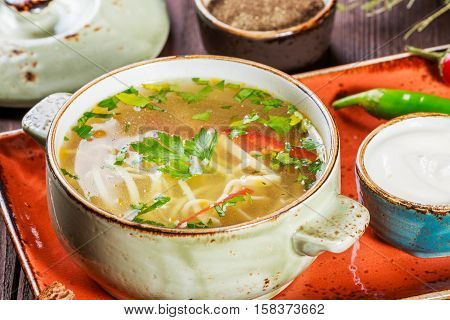 Vegetable soup broth with noodles herbs parsley and vegetables in bowl with sour cream spice pepper dried thyme and bread on dark wooden background. Ingredients on table