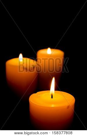 Close-Up of Three Lit Candles on Black Background