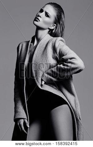 High fashion look.glamor beautiful sexy hot stylish blond woman model in overcoat in studio