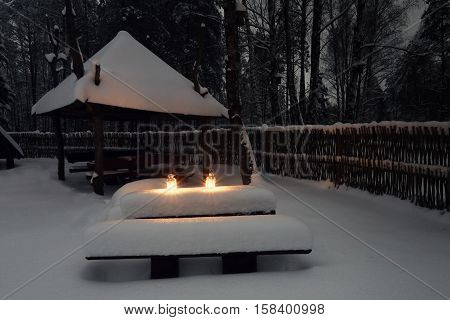 Snow in village at christmas night. White decorative lights with candles on snow. Xmas forest covered by snow.