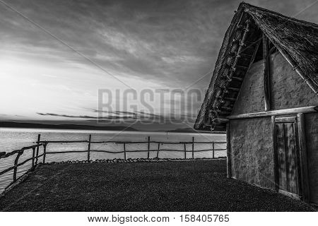 Black and white fishing hut at sunset - Image with a clay thatched house suspended on stilts over a lake with the sunset light behind it in monochrome settings