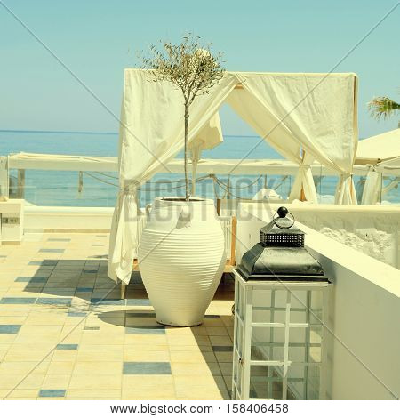 romantic terrace patio of seaside resort with outdoor furniture flower bawl and sea view, Crete, Greece. Square toned image