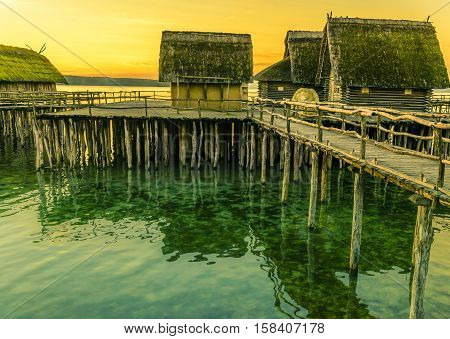 Fishing huts suspended on pillars - Fishing huts made from wood clay and thatched roof suspended on stilts over a lake water with the beautiful yellow sunset in the background