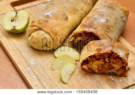 homemade cake - roll strudel. Lying on a wooden cutting board lightly sprinkled with flour. Nearby lies an apple. Space for text Christmas food. A festive meal. next to cut a piece of strudel