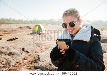 Portrait of a smiling young girl in jacket using mobile phone at campsite in autumn