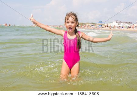 The Girl In The Pink Bathing Suit Joyfully Shouts And Gestures By Going Into The Water