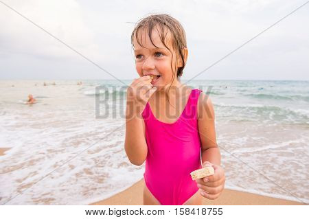 The Girl In The Pink Bathing Suit Standing On The Beach And Eating Waffle