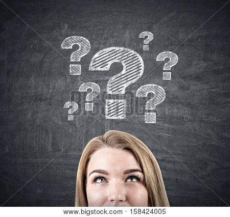 Close up of a blond woman's head near a blackboard with a white question mark sketches on it. Concept of too many questions
