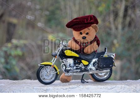 Teddy Bär with cap stands behind a motorcycle outside