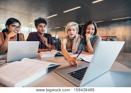College students using laptop while sitting at table. Group study for school assignment.