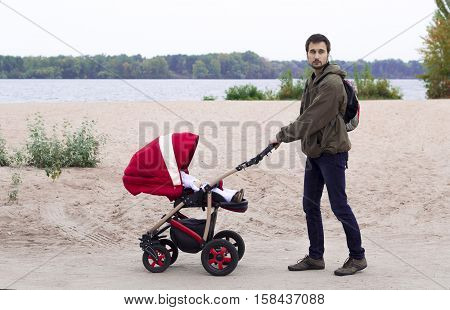 The father walks with the baby in the baby carriage in the park by the river