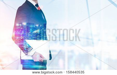 Close up of a businessman's torso holding a laptop and standing in his office. Skyscrapers at night in the foreground. Toned image. Mock up. Double exposure