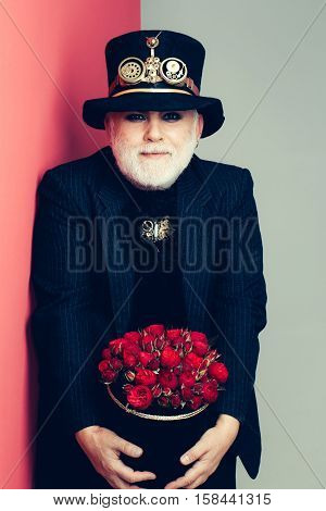 Frown senior bearded man or watchmaker with white beard in black hat with watch mechanical metallic gears and cogwheels holds box with flowers on colorful wall