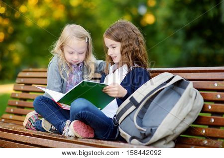 Two Adorable Little Schoolgirls Studying In A City Park