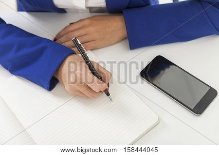 Top view of woman's hands taking notes. She is wearing blue blazer and sitting at the table with laptop and smartphone. Mockup