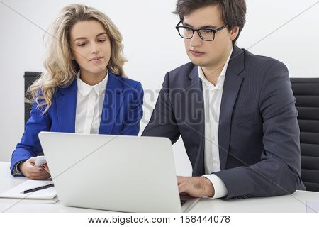 Portrait of beautiful blond girl in blue blazer and a young guy wearing glasses working at one laptop in office. Concept of cooperation