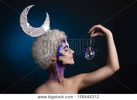 Winter Portrait Of A Girl With Creative Make-up. The Moon In Her Hair. Beautiful Female Profile.