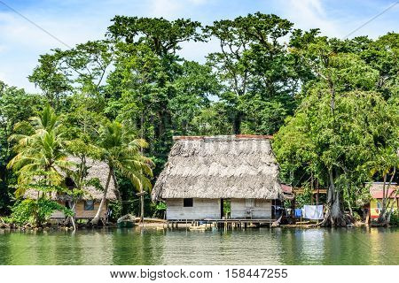 Wooden houses on stilts with palm leaf roofs on riverbank in Guatemala, Central America