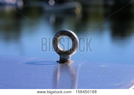Large metal eyelet attached to a metal electrical box on the shore of a quiet cove.