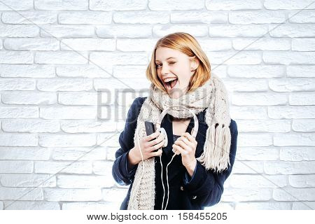 young pretty woman or fashionable sexy smiling girl with cute face and blonde hair in coat and scarf ready to listen to music in headset with mobile phone mp3 player on white brick wall background