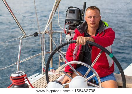 Skipper at the helm controls of a sailing yacht. Lifestyle, sport and leisure.