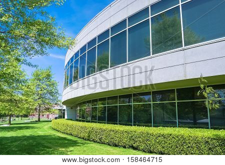 Green hedge and mowed lawn along round shaped wall of the office building