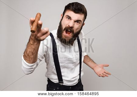 Young handsome man in suit with suspenders shouting holding cigar over white background. Copy space.