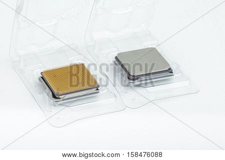 Two CPU in the open box. The first processor is upside. The second processor is turned bottom up. Isolated on white background.